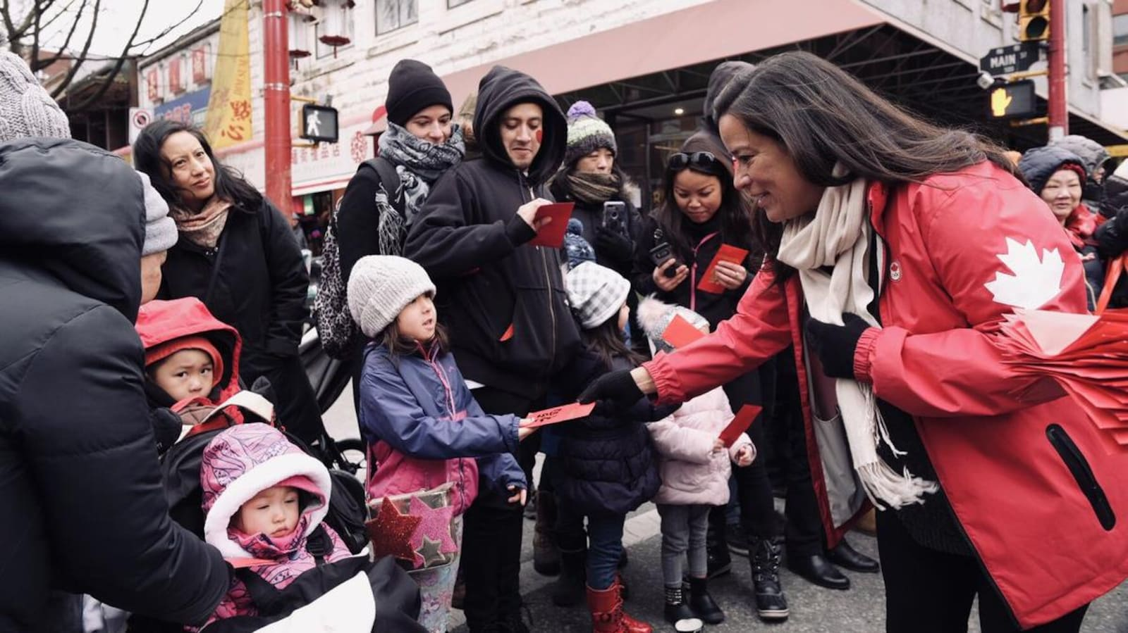 Une femme dans la quarantaine en veste rouge avec une feuille d'érable donne des feuilles rouges à des enfants et des adultes dans une rue lors d'un défilé.