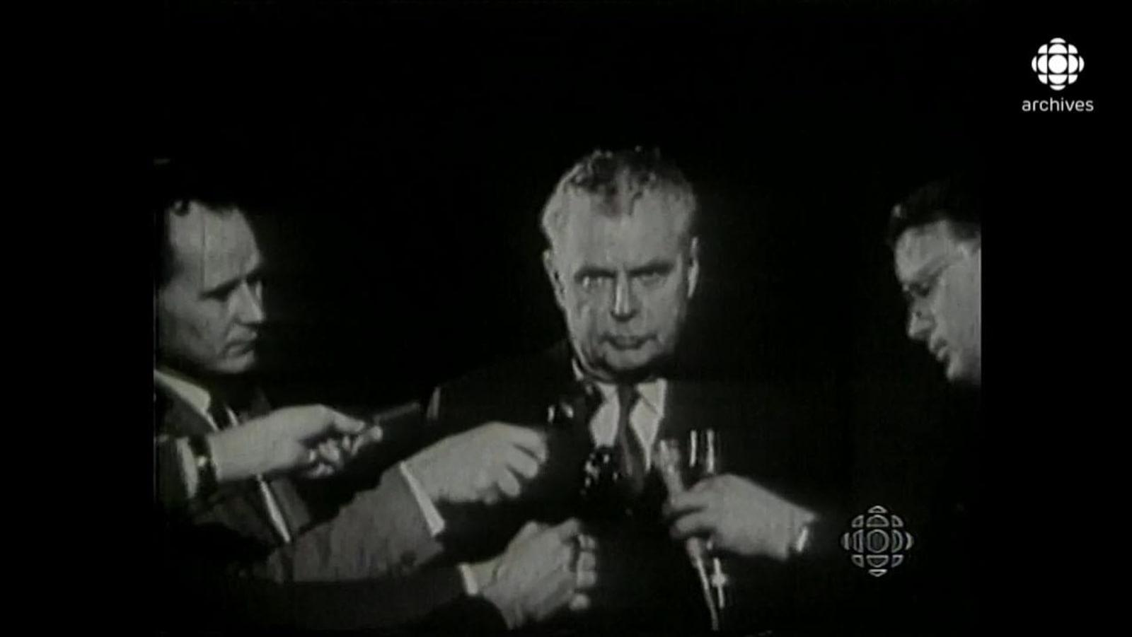 En noir et blanc, John Diefenbaker, entouré de micros et de journalistes, regardant sévèrement la caméra