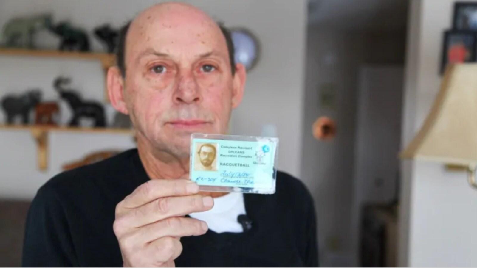 Un homme montre son permis de conduire.