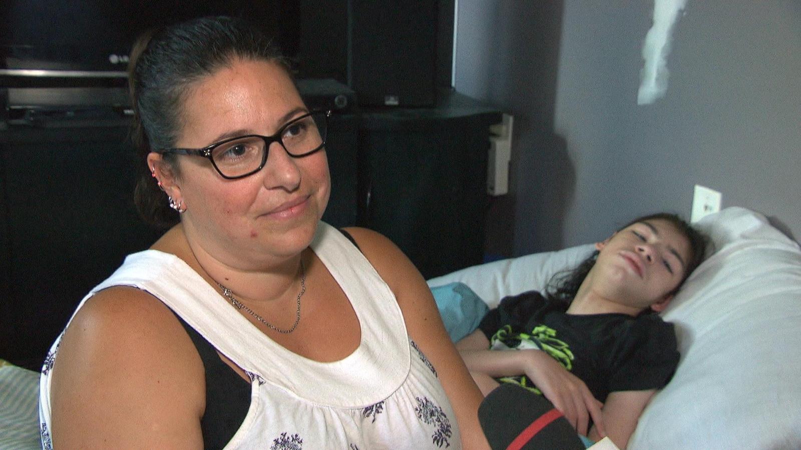 Julie-Anne Perron répond aux questions d'une journaliste. Son fils, Justin, est dans un lit en arrière plan.