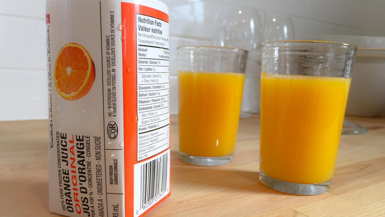 Image d'un contenant de jus d'orange congelé, ainsi que deux verres pleins, sur le comptoir d'une cuisine.
