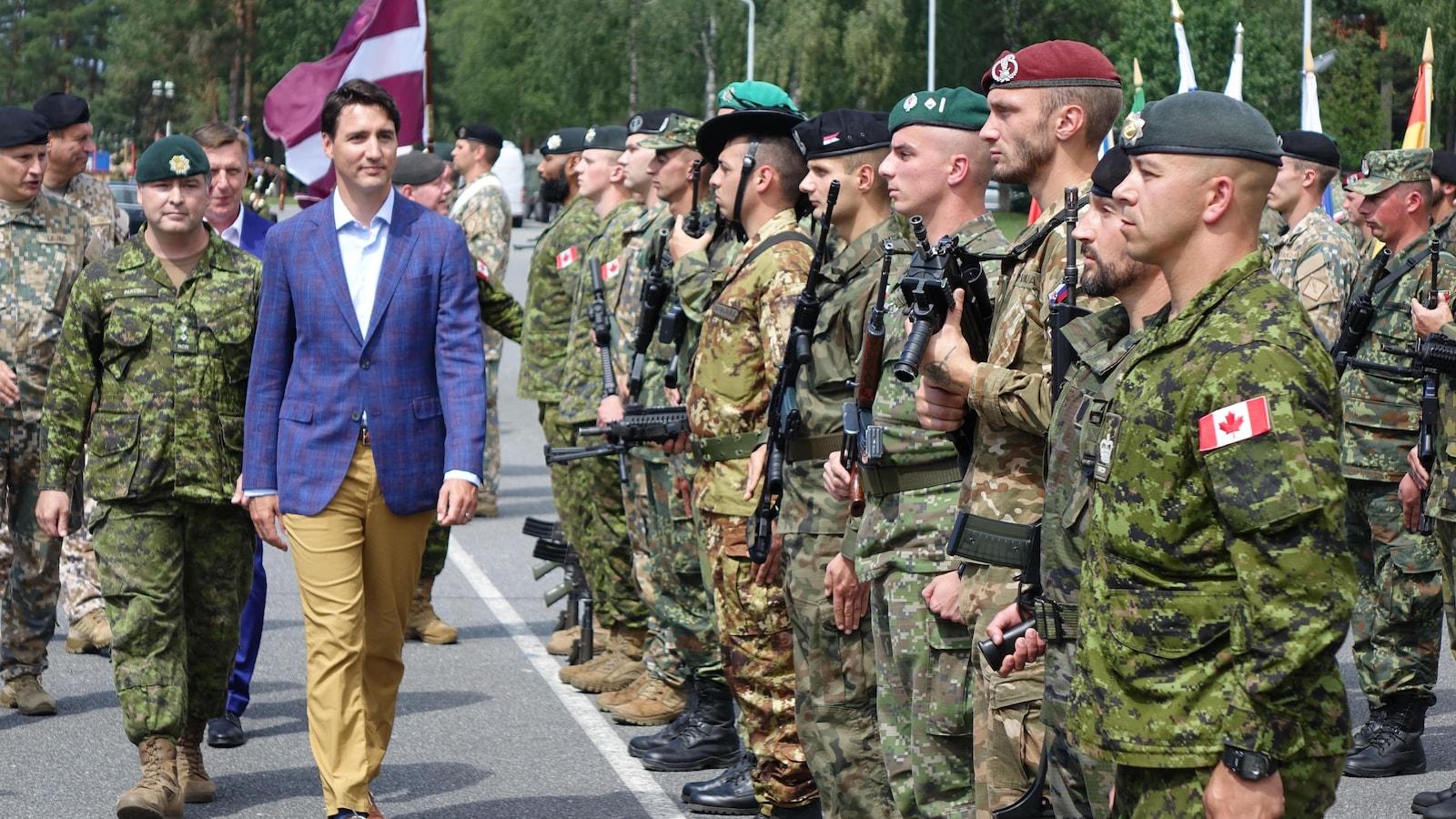 Justin Trudeau inspecte les troupes de l'OTAN dont les soldats sont en rang.