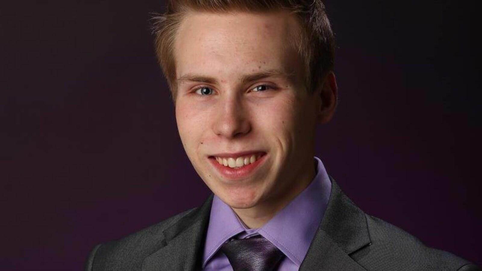 Le jeune homme pose pour une photo professionnelle vêtu d'un veston.