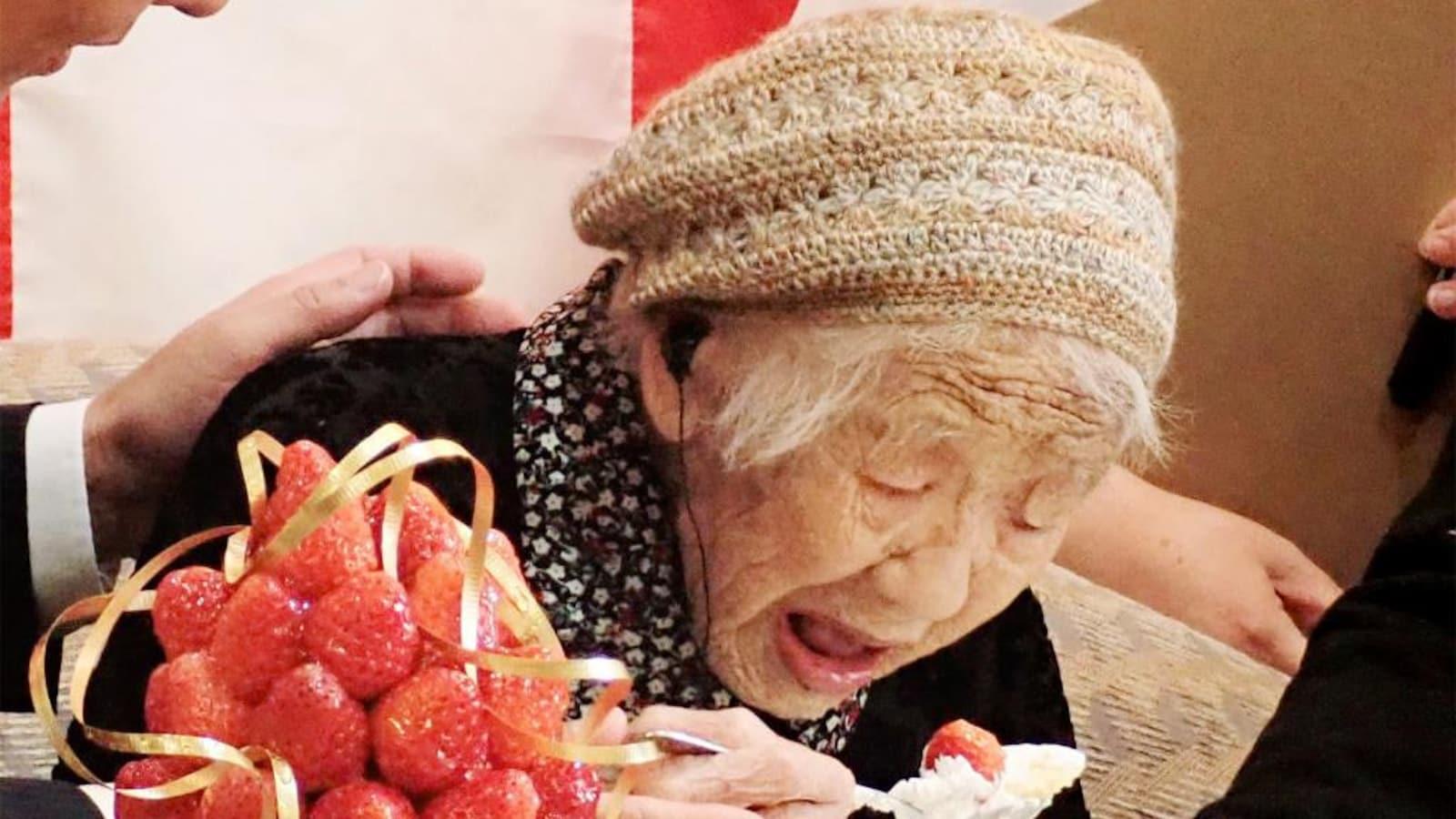 La doyenne de l'humanité, un chapeau sur la tête et une cuillère à la main, se penche devant une assiette, la bouche ouverte, pour manger une part de gâteau à la fraise.