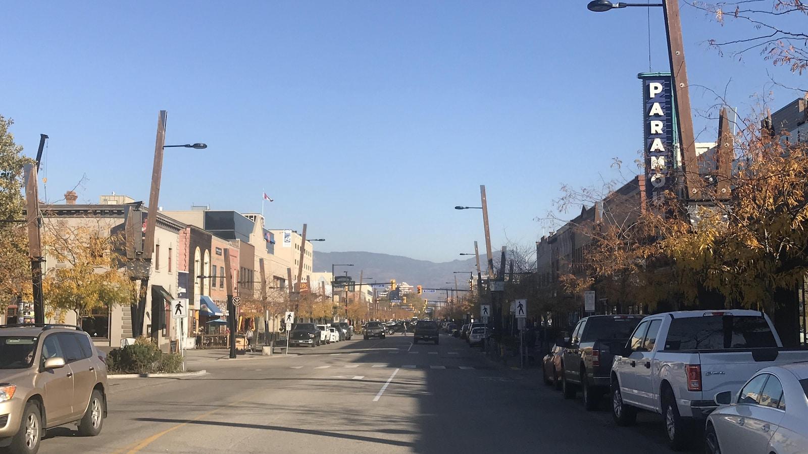 Une rue avec des voitures qui roulent et d'autres qui sont garées, et les montagnes au loin.