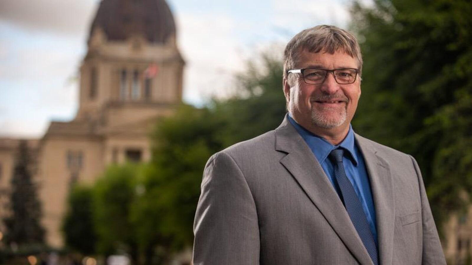Le chef du Parti progressiste-conservateur de la Saskatchewan, Ken Grey, se tient debout dehors en costume-cravate devant l'Assemblée législative