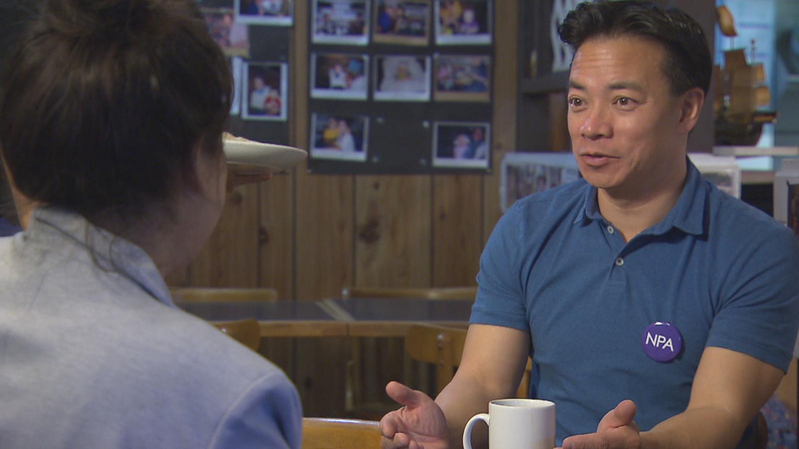 Ken Sim parle à la journaliste avec une tasse de café devant lui.