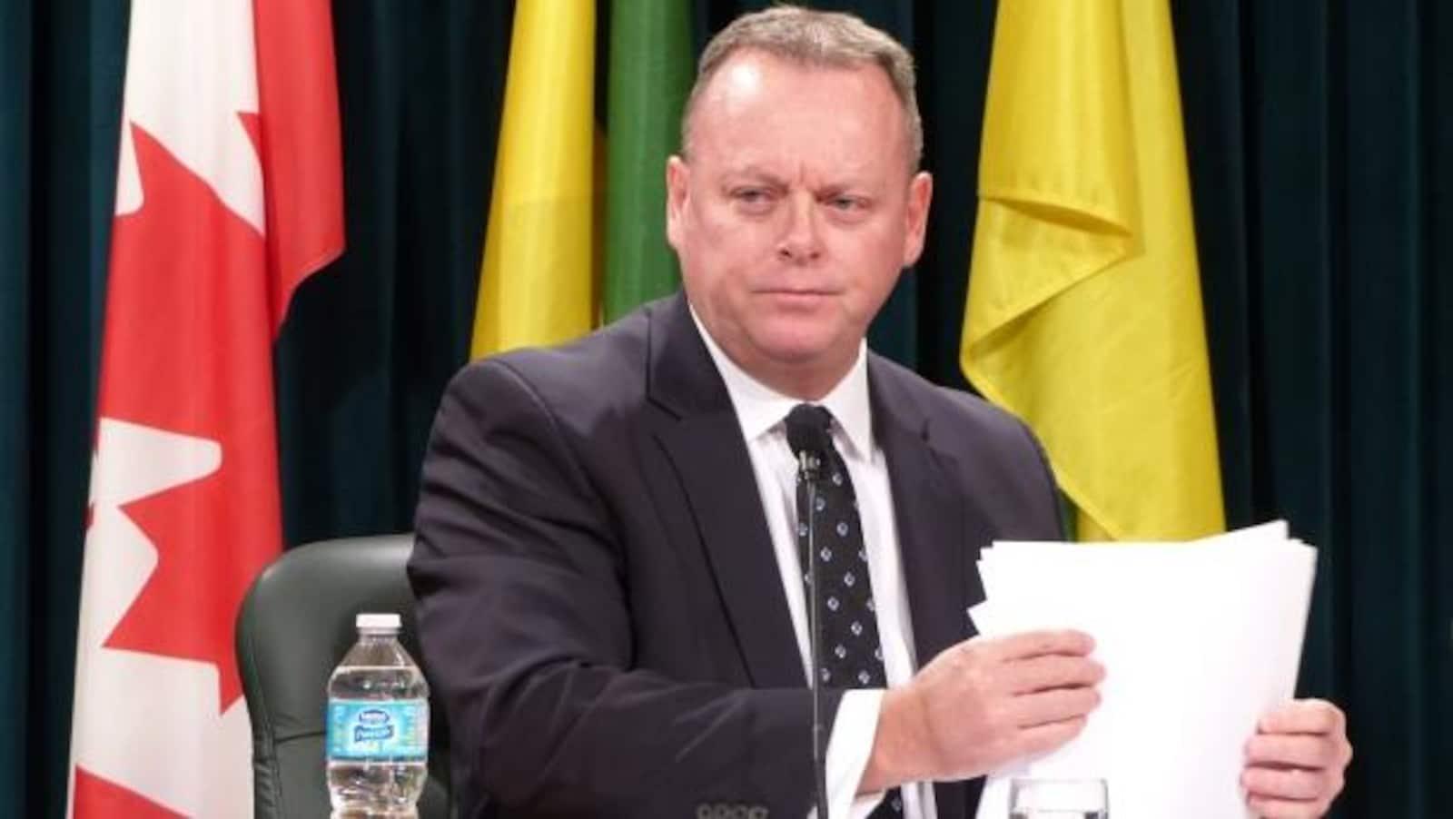 Le ministre des Finances de la Saskatchewan est assis à une table et tient des feuilles blanches. En arrière-plan, les drapeaux du Canada et de la Saskatchewan.