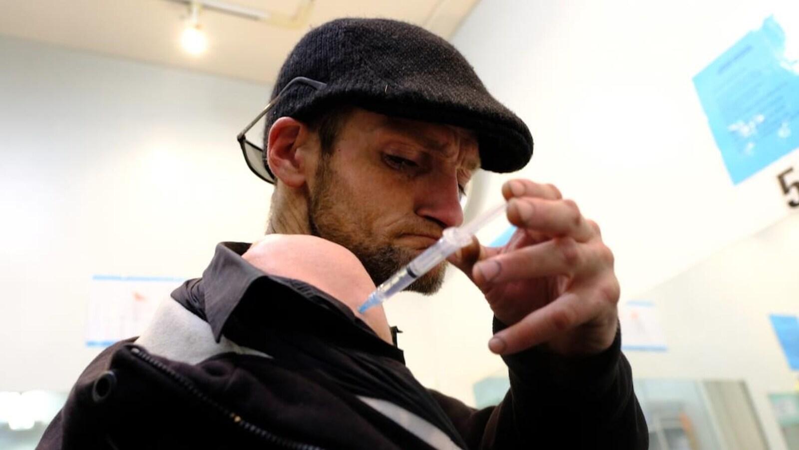 Kieran Collins s'injecte de l'héroïne dans l'épaule.