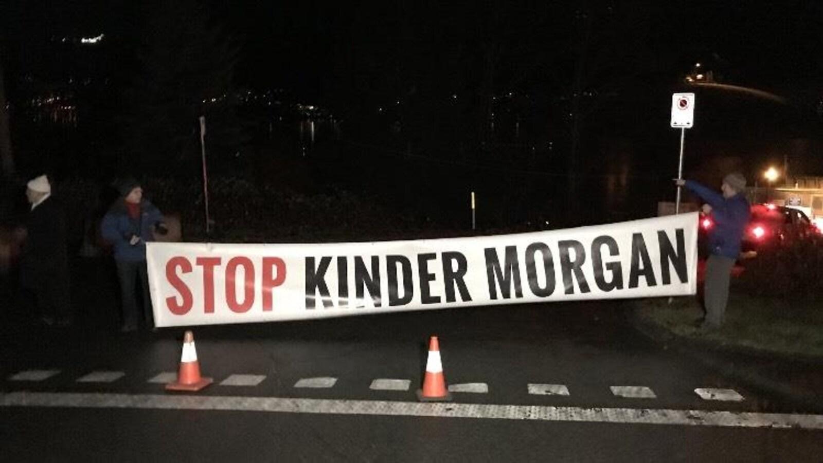 Deux hommes tiennent une banderole où il est écrit, Stop Kinder Morgan.