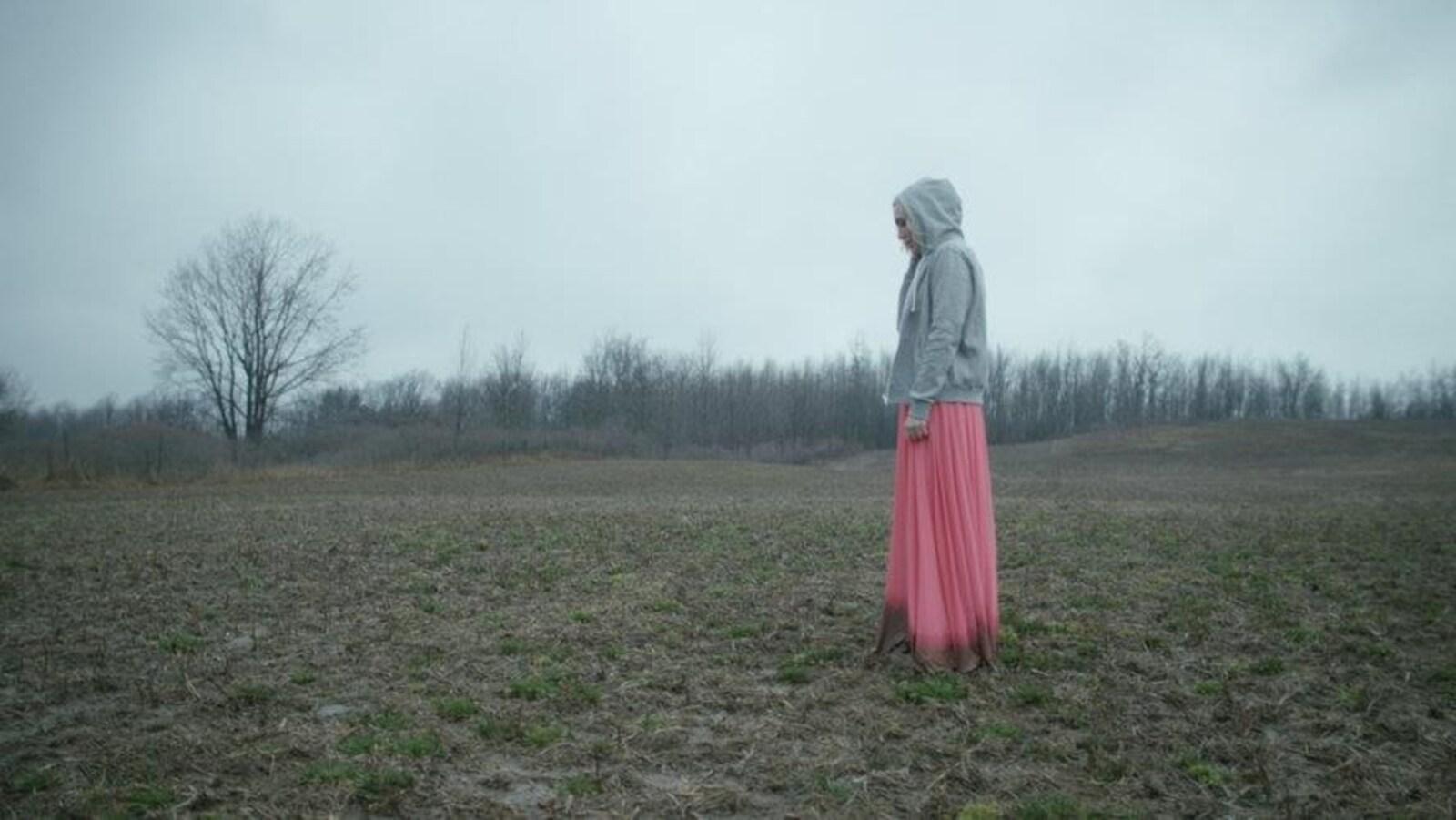 Une femme avec une robe rose est debout dans un champ gris et terne.