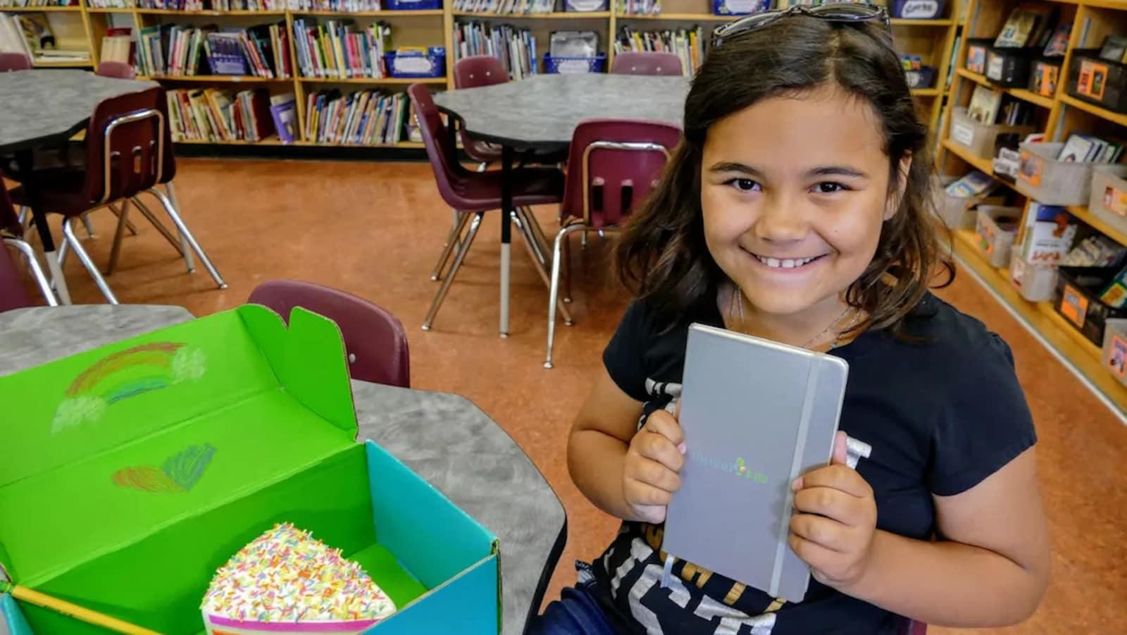 Une fillette tient un livre dans ses mains.