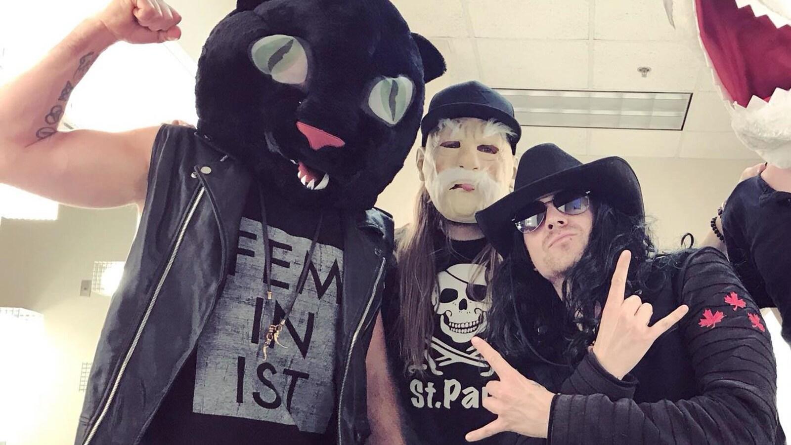 Quatre hommes costumés prennent la pause, l'un d'entre porte une tête de chat en peluche et un débardeur imprimé du mot de «feminist». Il lève le bras en serrant le poing.