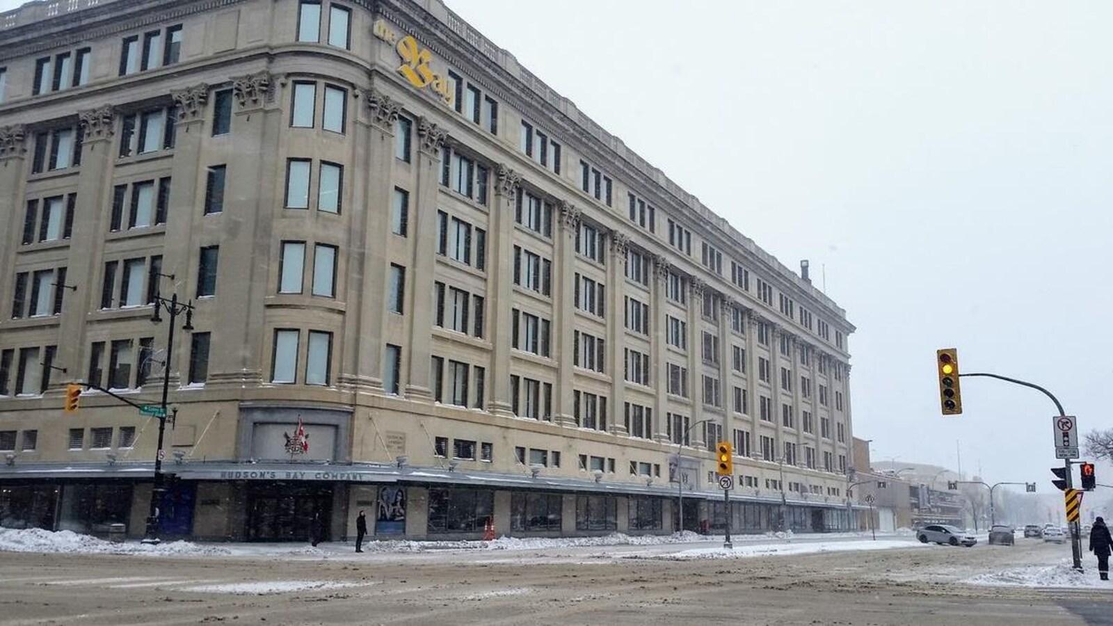 Un grand immeuble brun-gris, vu de l'extérieur, à l'angle de deux rues passantes, un jour de neige.