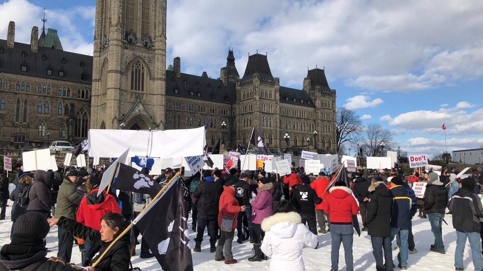 Des personnes avec des pancartes devant l'édifice central du Parlement à Ottawa.