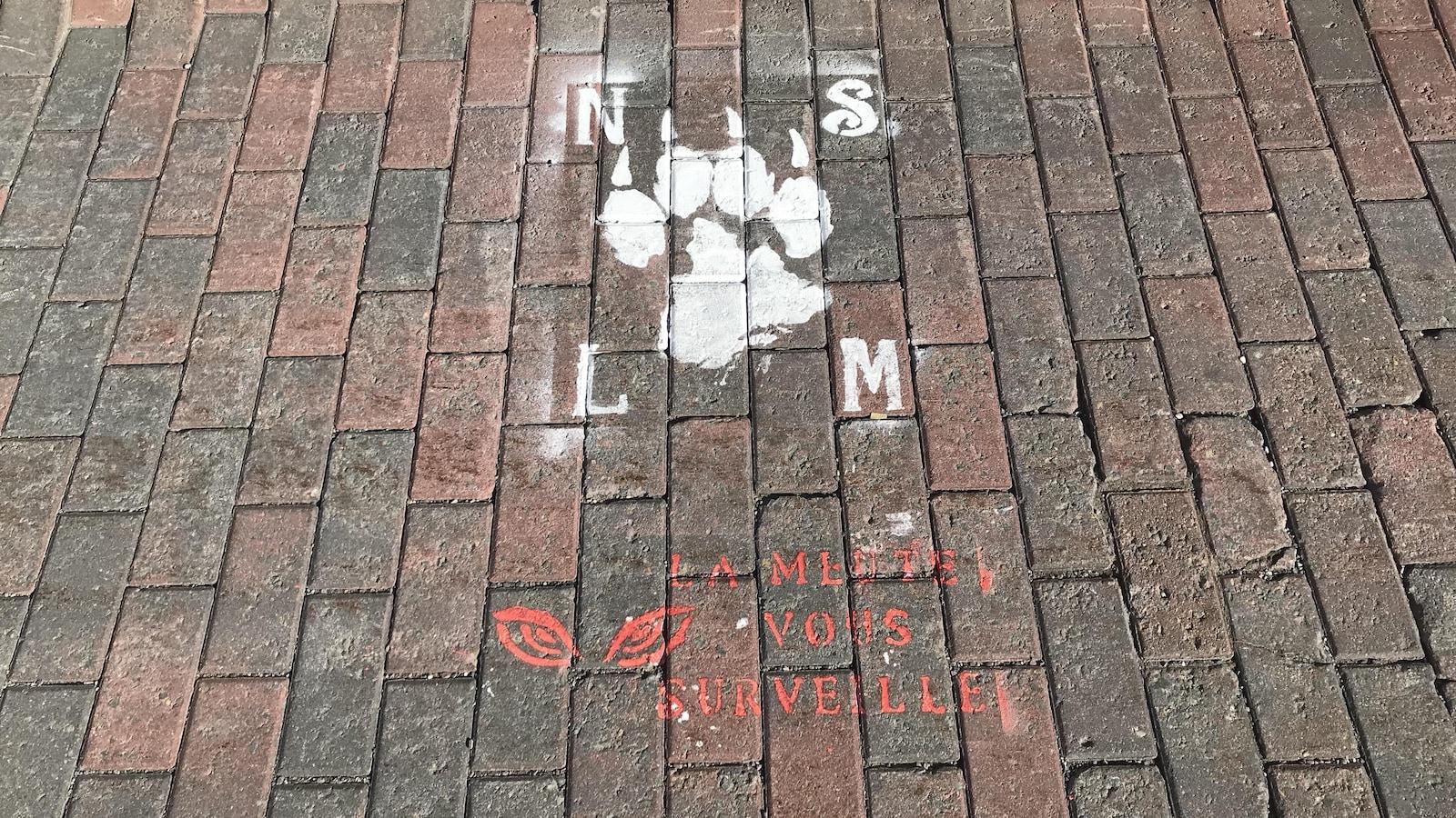 Le logo du groupe identitaire La Meute avec la phrase «La Meute vous surveille».