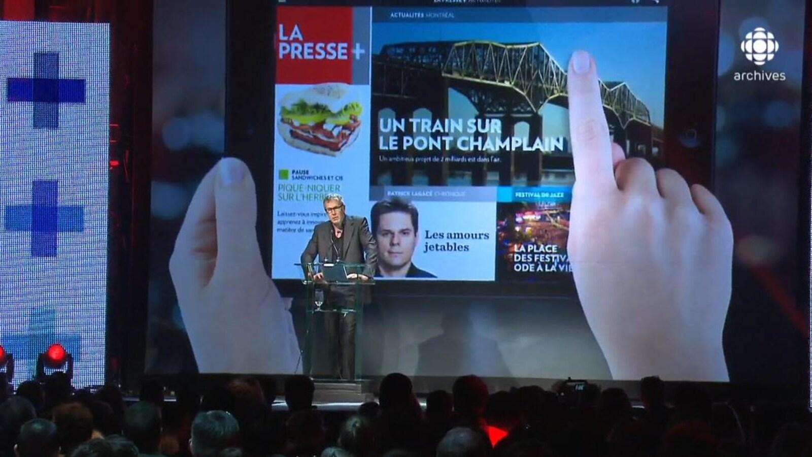 Guy Crevier présentant sur une scène, avec en arrière-plan un écran géant présentant un tutoriel de du journal numérique La Presse+.