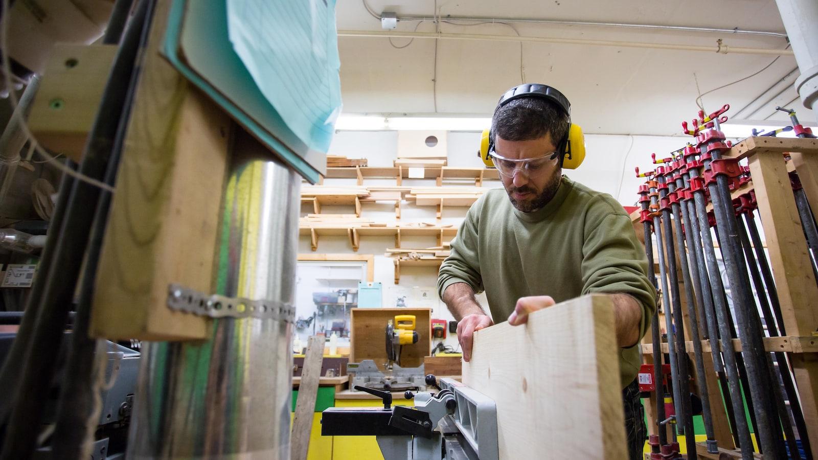 Un homme utilise de la machinerie dans un atelier de menuiserie.