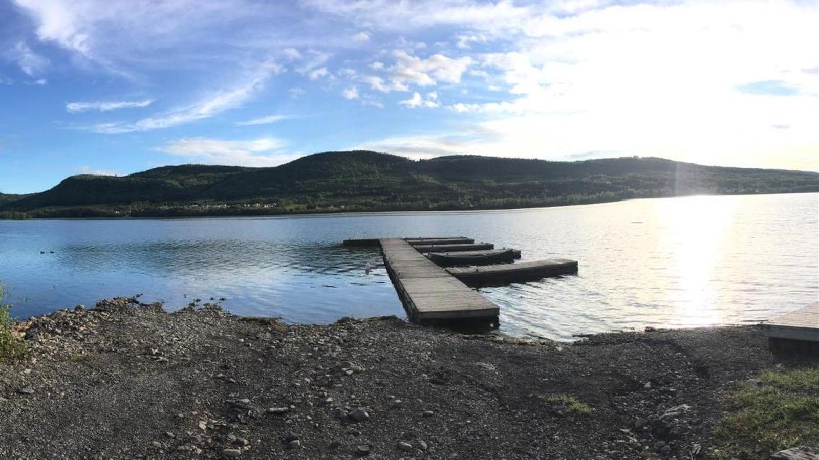 Un quai flotte sur l'eau du lac. De l'autre côté, on peut voir des collines verdoyantes.