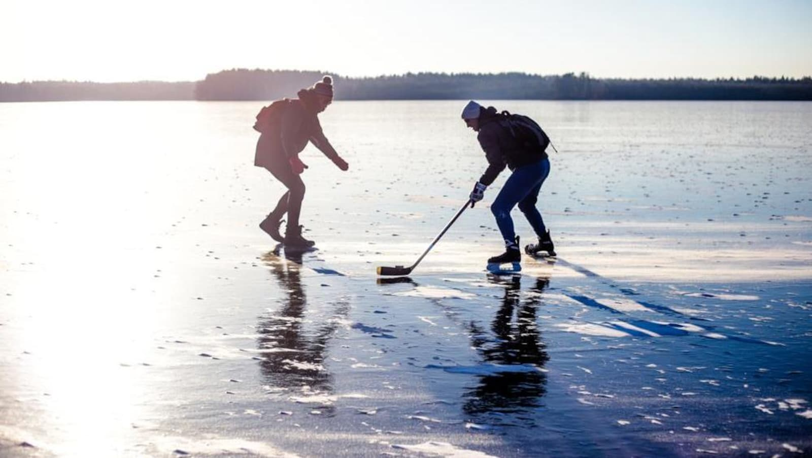 Deux personnes jouent au hockey sur un immense lac gelé.