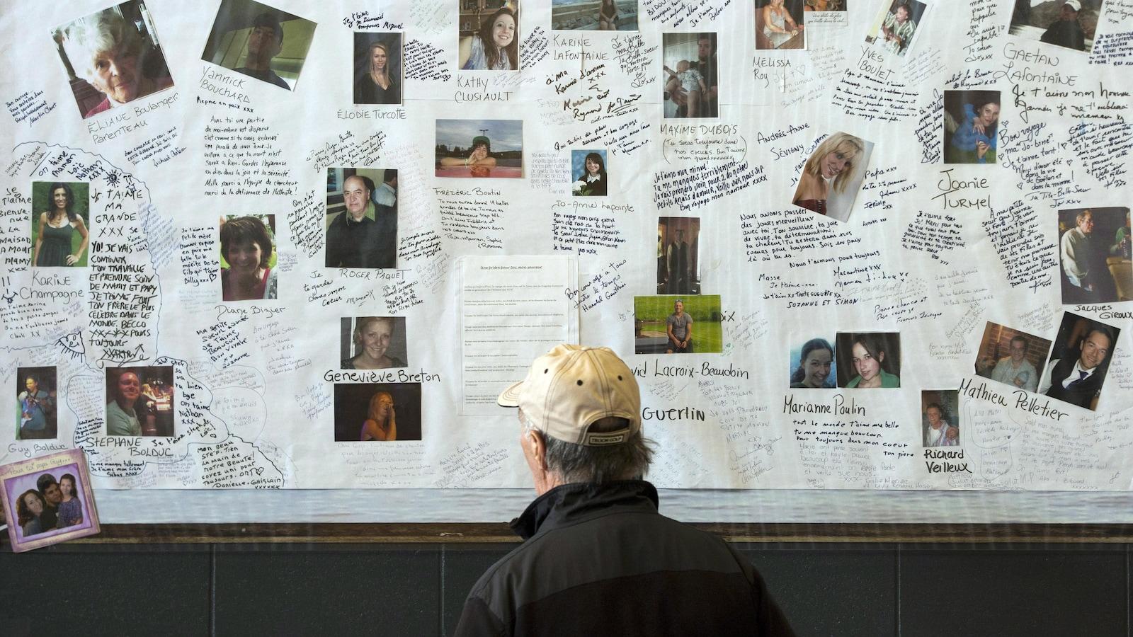 Un homme regarde des photos des victimes de la tragédie de Lac-Mégantic.