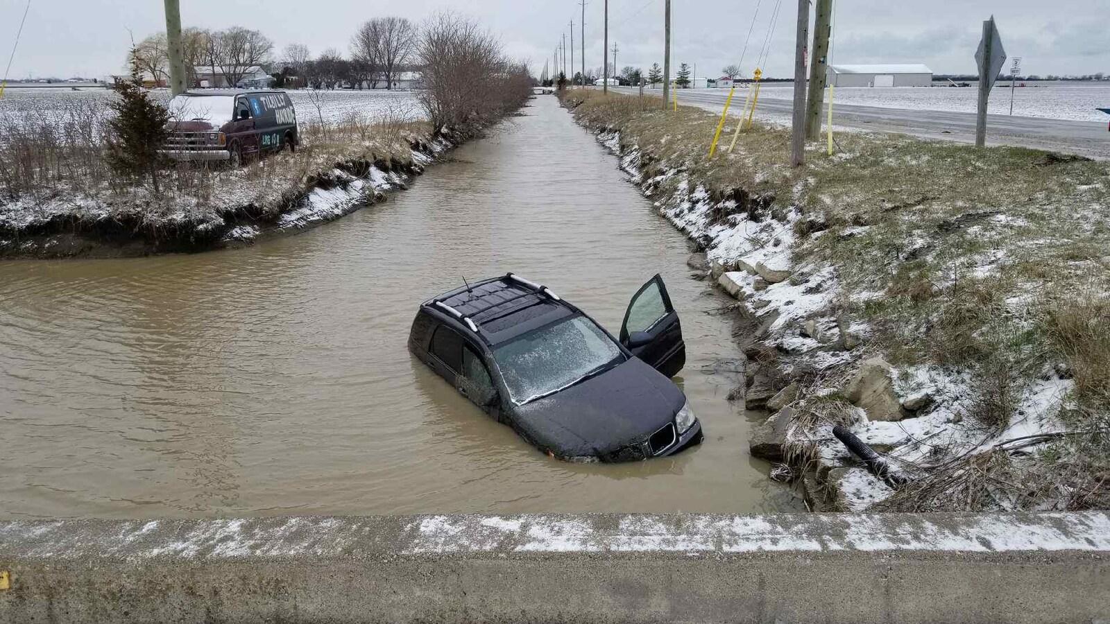 Une voiture a glissé sur la chaussée et s'est retrouvée dans un fossé rempli d'eau.
