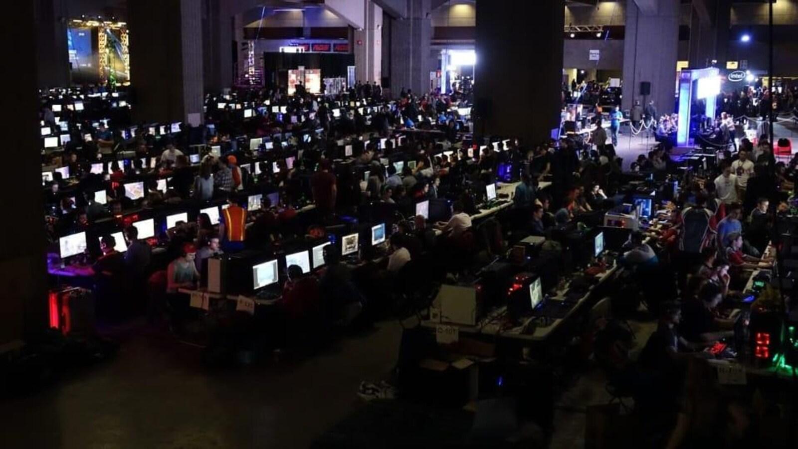 Quelques centaines de joueurs fourmillent dans une grande salle au travers des  rangées où sont installé les ordinateurs.