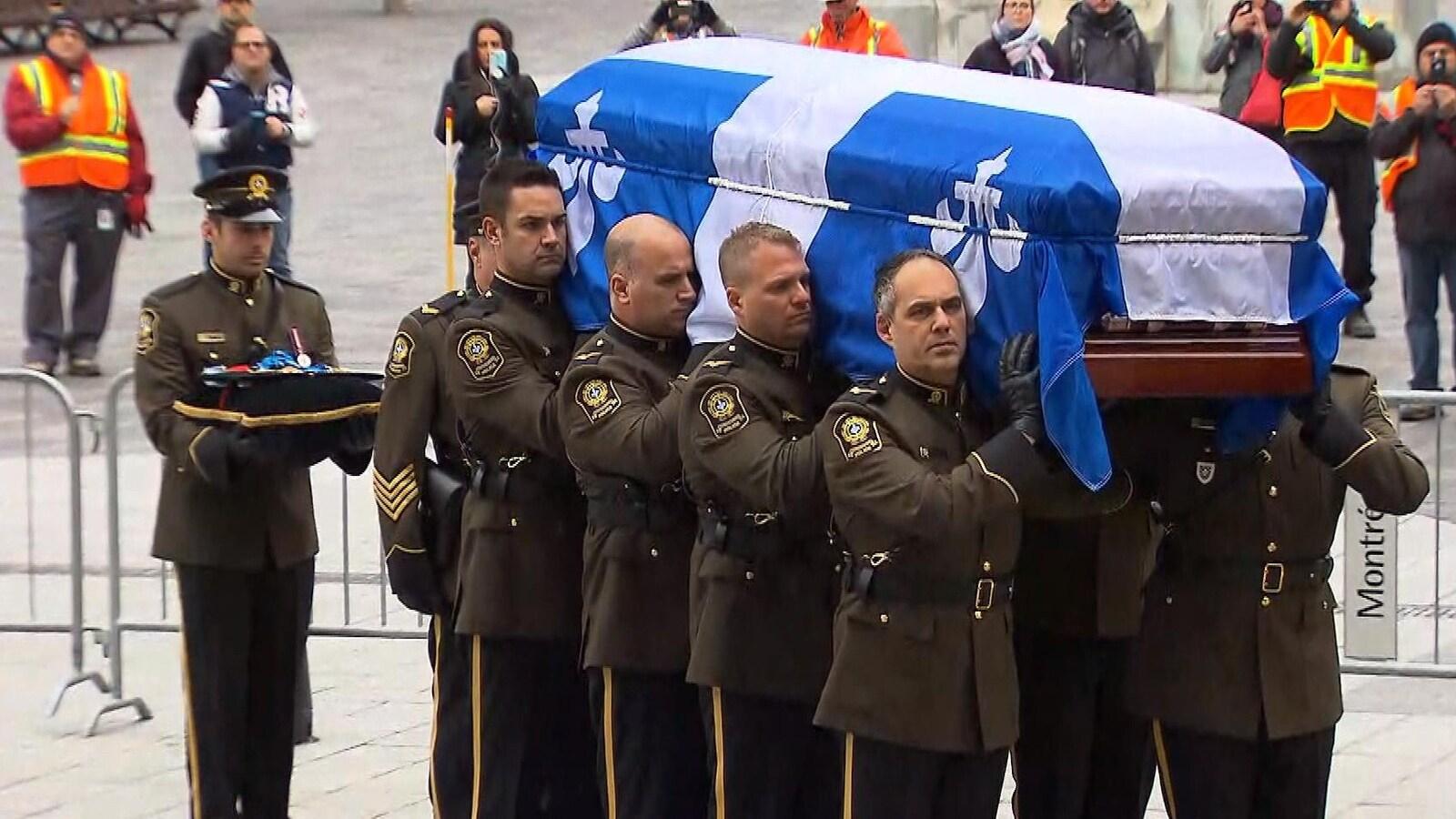 Un cercueil déposé sur les épaules de porteurs.