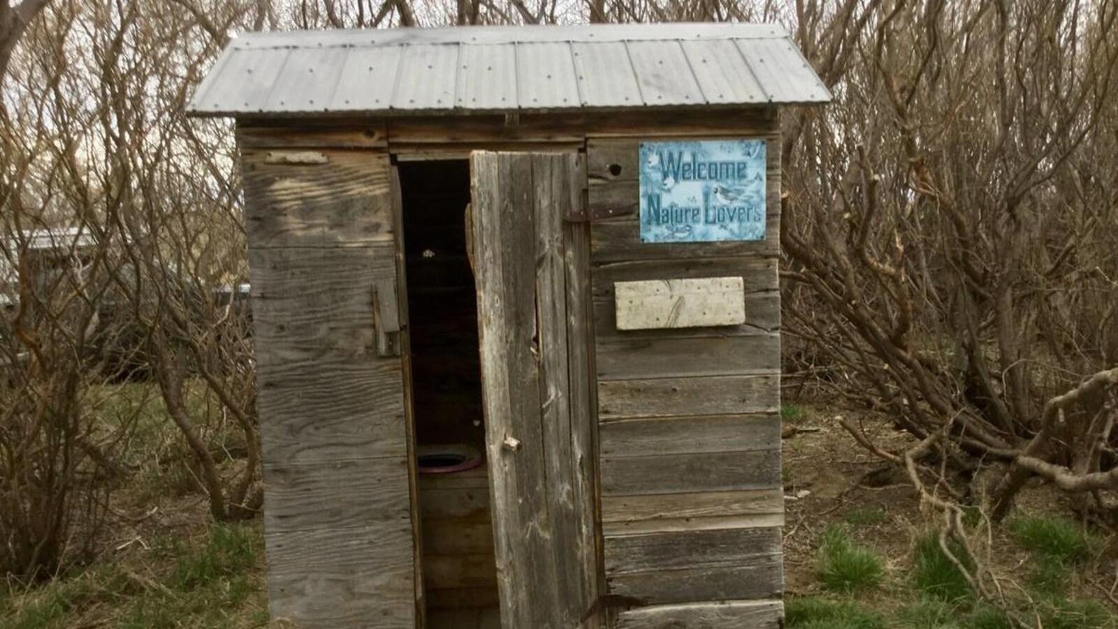 Une latrine en bois dans un bosquet.