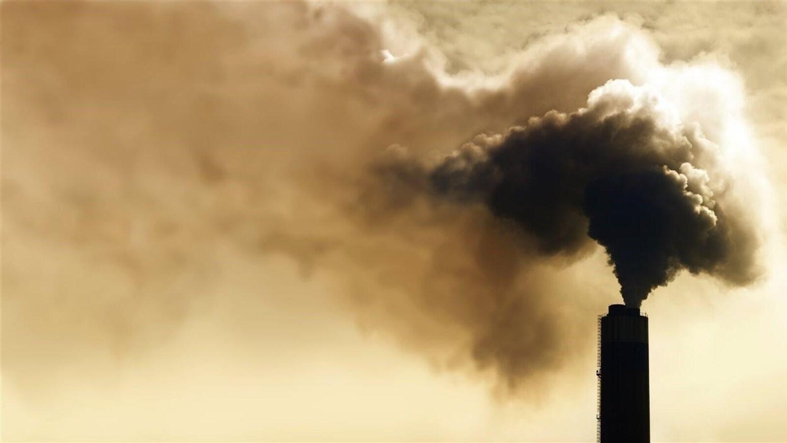 Une cheminée éjecte une grande quantité de fumée.