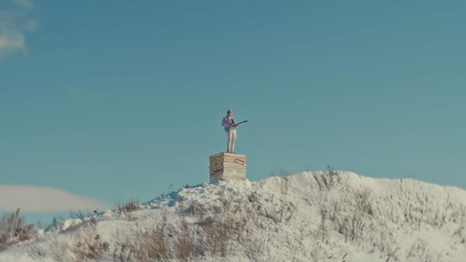 Un homme se tient sur une caisse posée sur une colline enneigée.