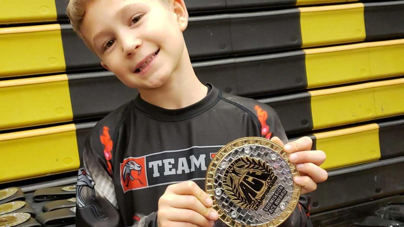 Une jeune garçon tient une médaille dans ses mains.