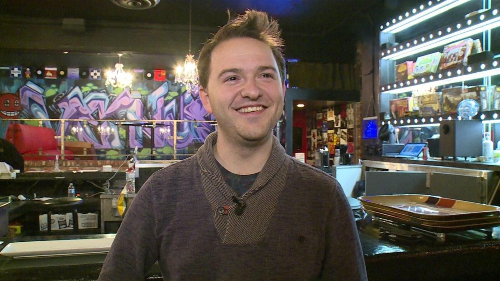 Portrait d'un homme souriant dans un bar