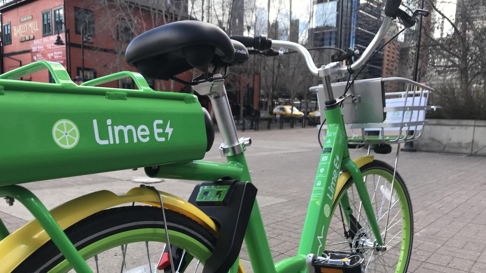 Un vélo vert vif stationné au coeur d'édifices du centre-ville de Calgary.