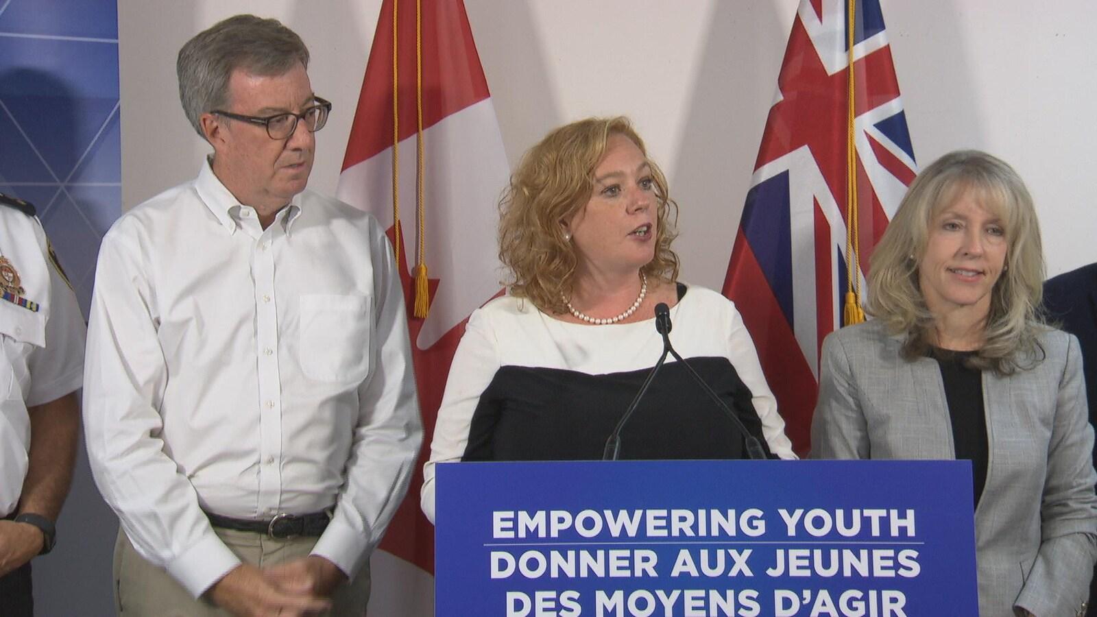 Jim Watson (à gauche), Lisa MacLeod (au centre) et Merrilee Fullerton (à droite) derrière un podium avec un micro pendant un point de presse.