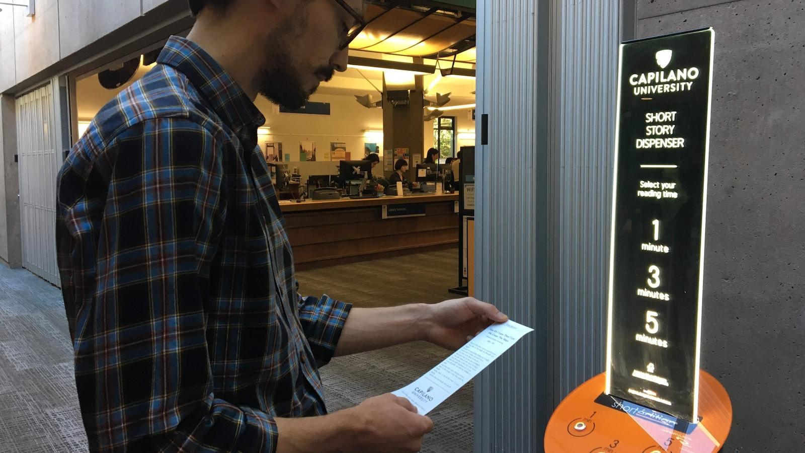 un homme debout qui tient un bout de papier devant une borne