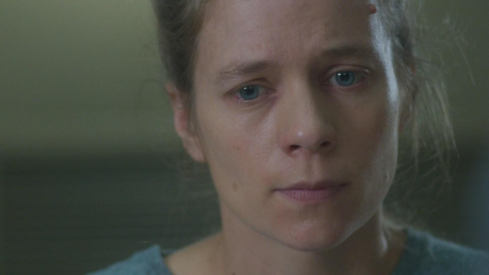 L'actrice Livia Sassoli regarde dans le vide, les larmes aux yeux.