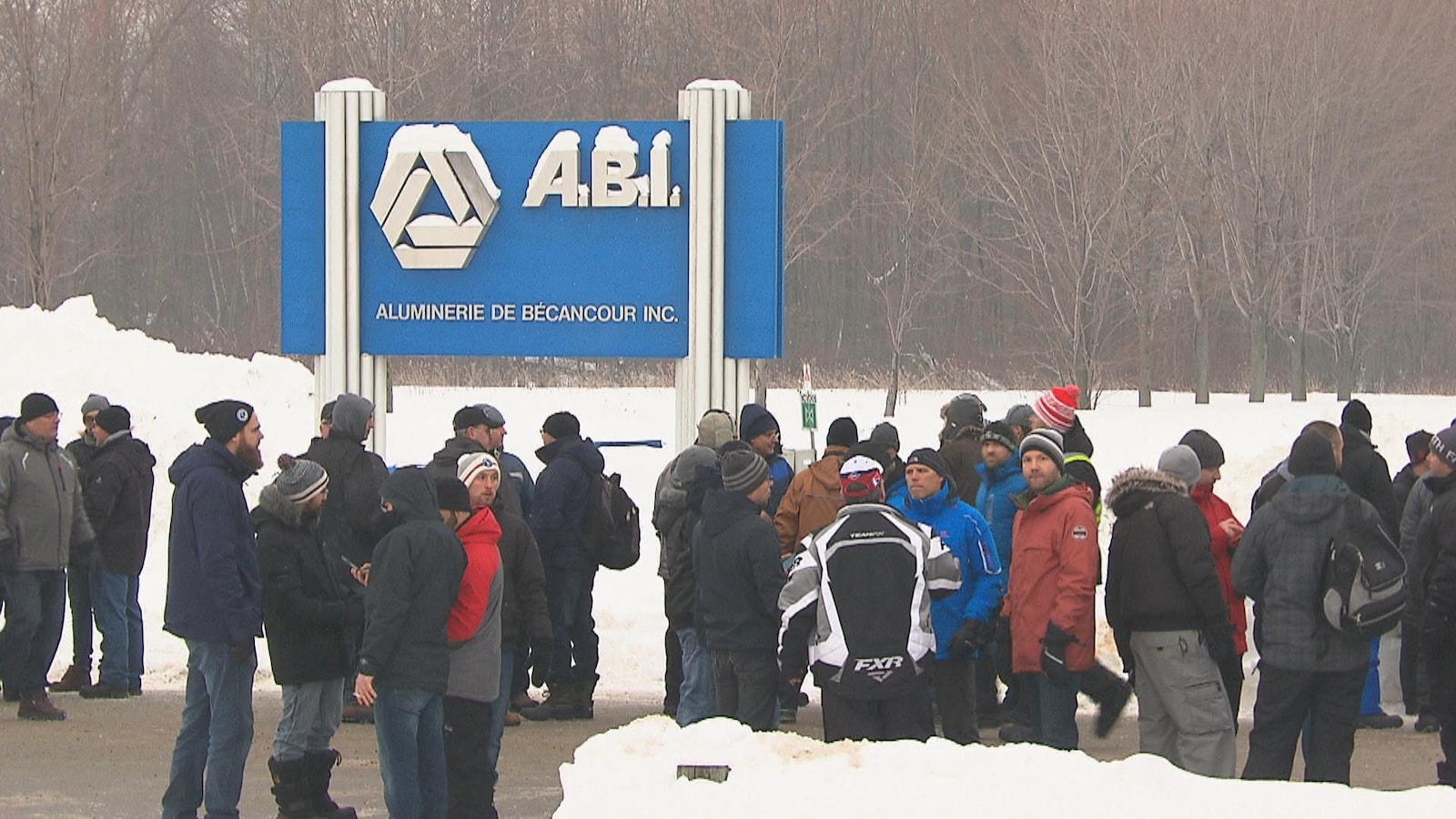 Gens rassemblés en face de l'aluminerie, l'hiver, près de la pancarte ABI extérieure.