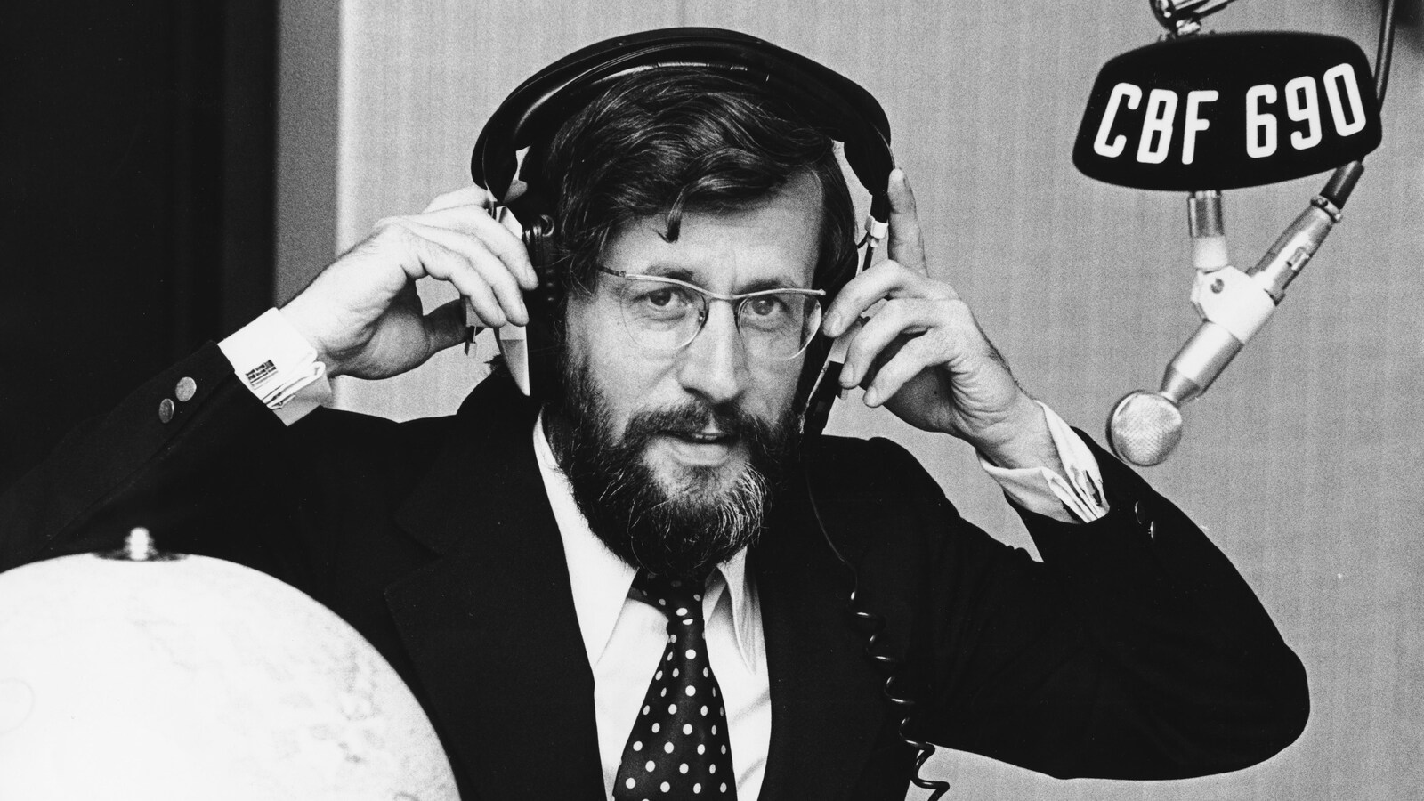 Dans un studio de radio, l'animateur Louis Martin ajuste un casque d'écoute sur sa tête. Un micro, portant une affichette avec la mention «CBF 690», est suspendu devant lui.