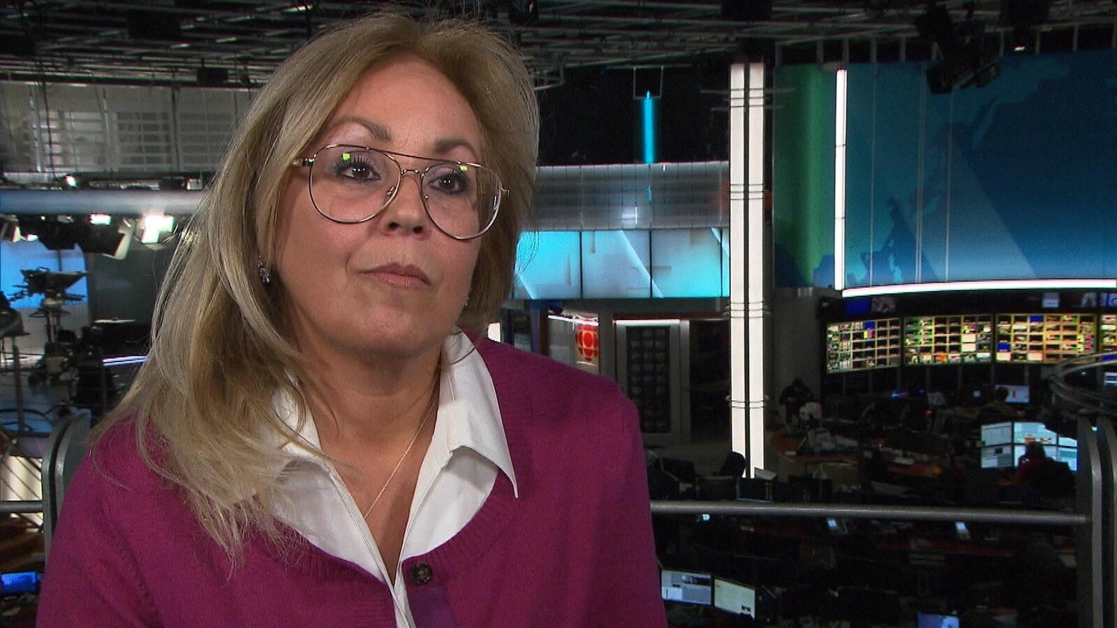 Une femme portant des lunettes est interviewé dans la salle de nouvelles de Radio-Canada.