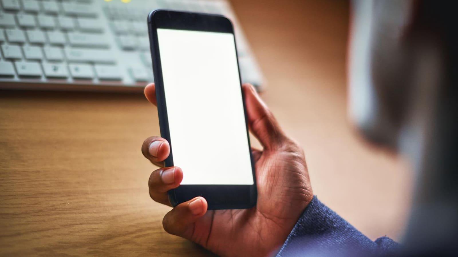 Un homme de profil regarde son cellulaire dans la pénombre.