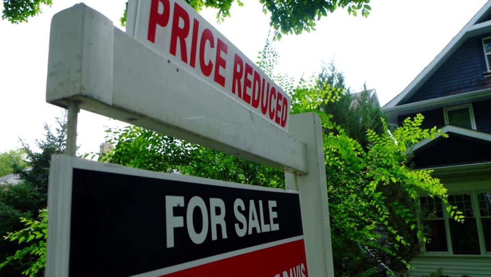 Maison avec en gros plan la pancarte annonçant sa vente