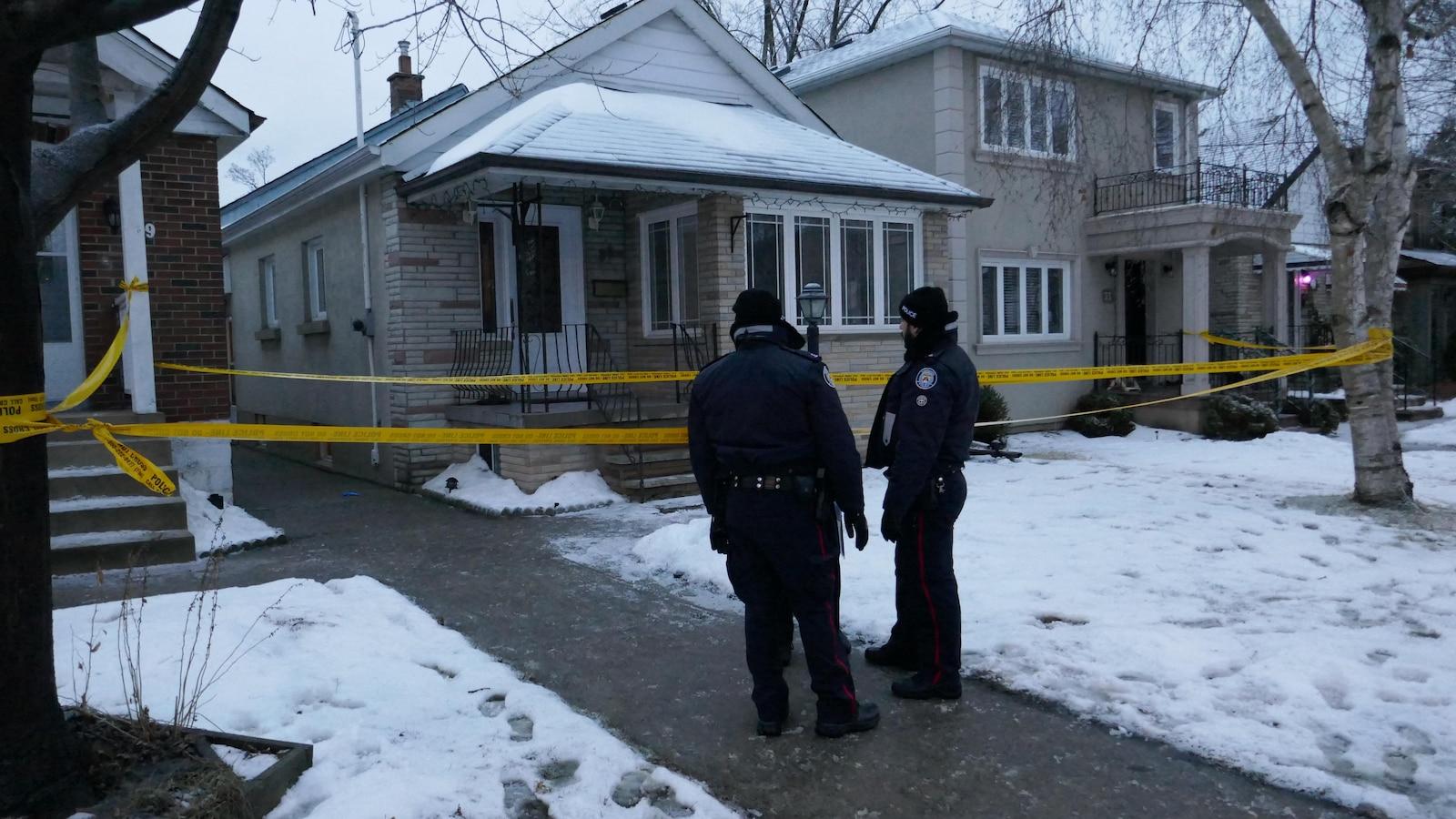 Photo de deux policiers debout dehors dans la neige devant une maison entourée d'une banderole de police jaune.