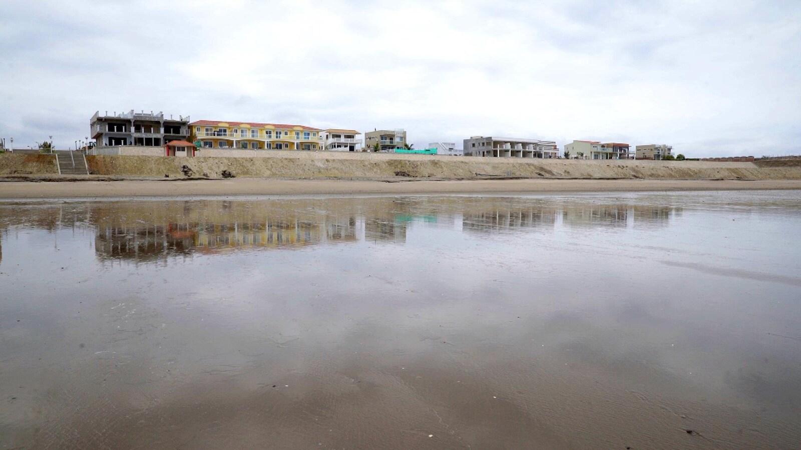 Des maisons alignées sur le front de mer. Elles se reflètent sur le sable humide.