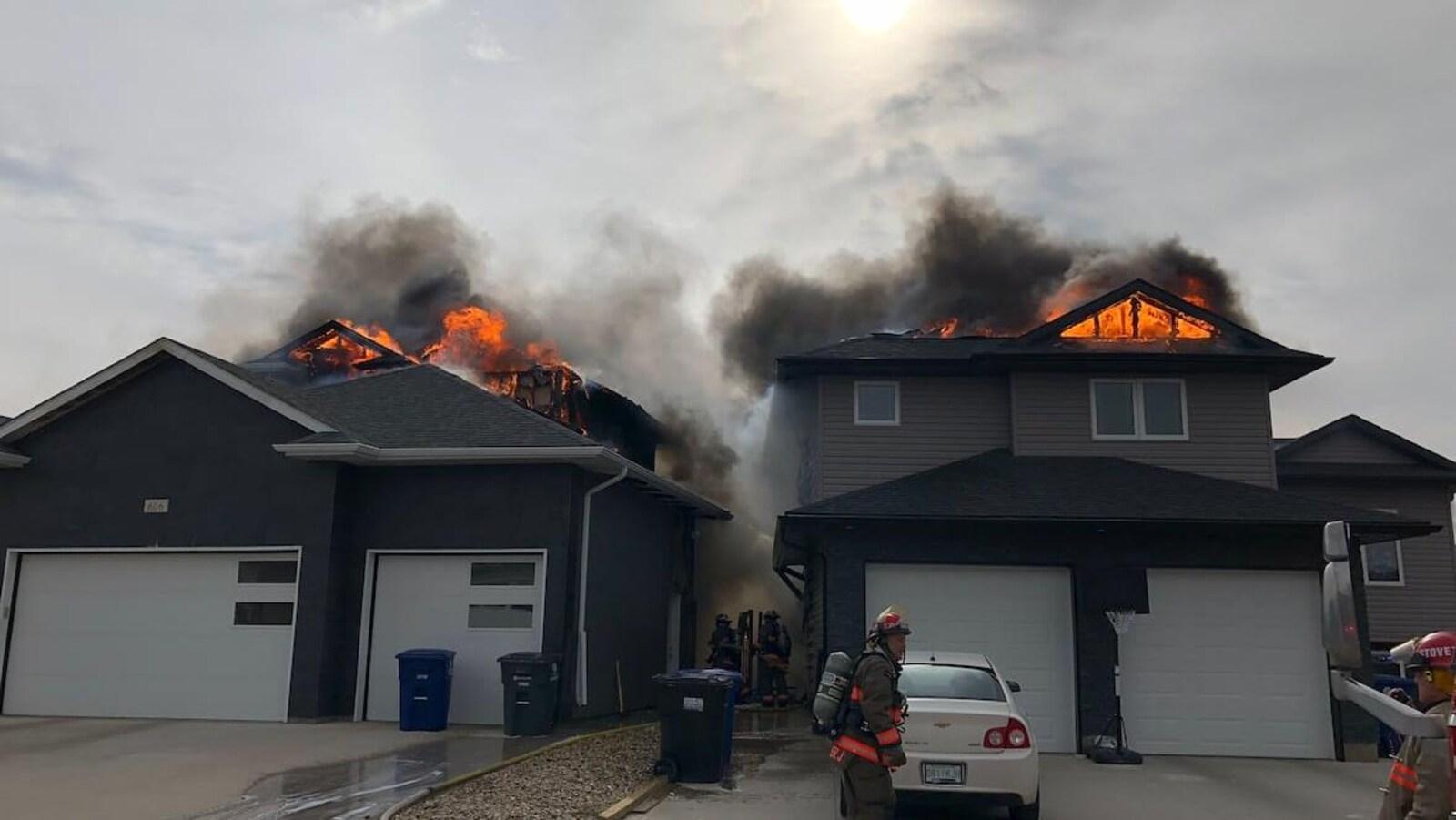 Des pompiers se tiennent près des deux maisons en feu.