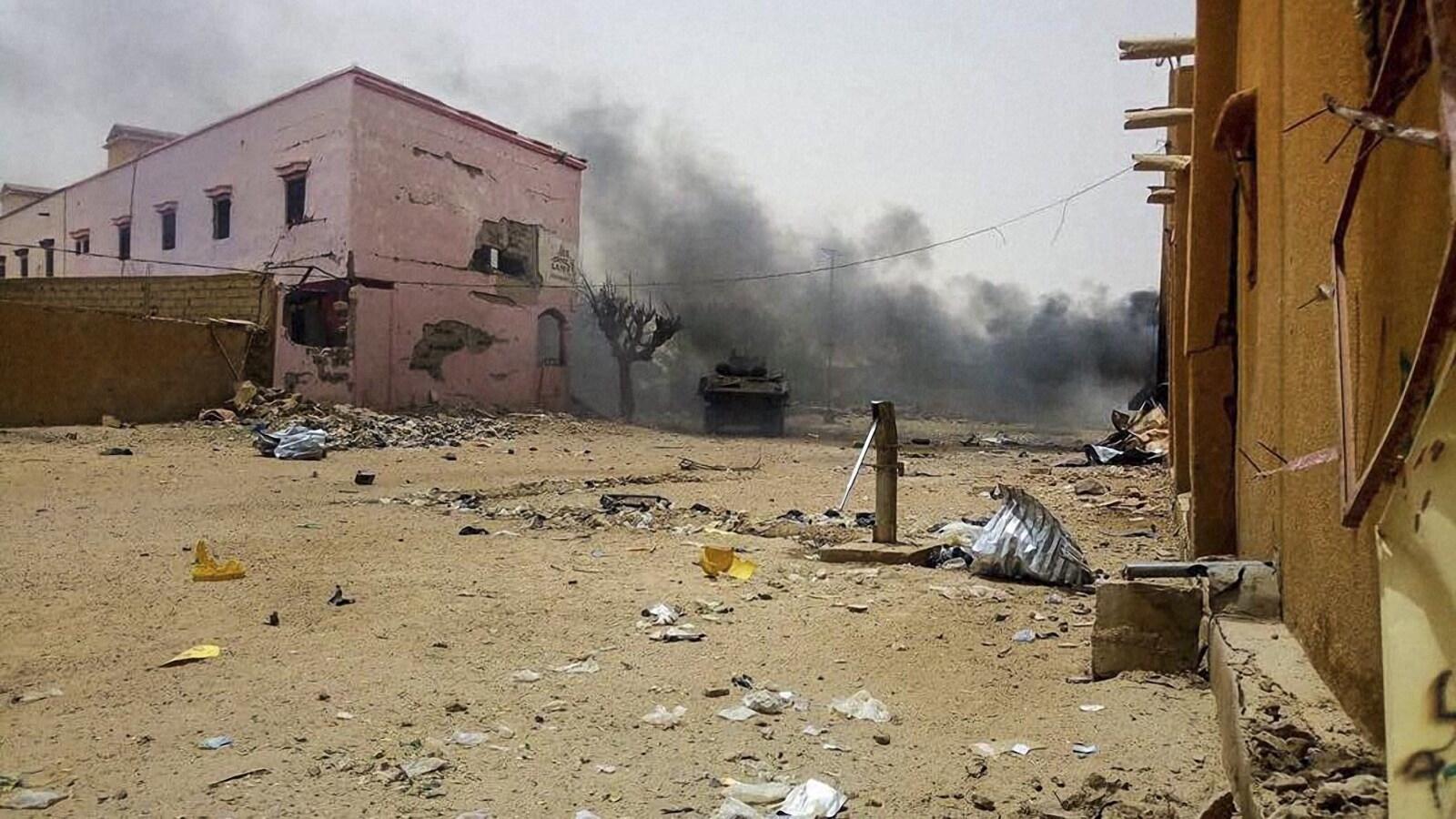 Un char d'assaut roule dans ville en ruine, les bâtiments ont été bombardés et le sol est jonché de débris.
