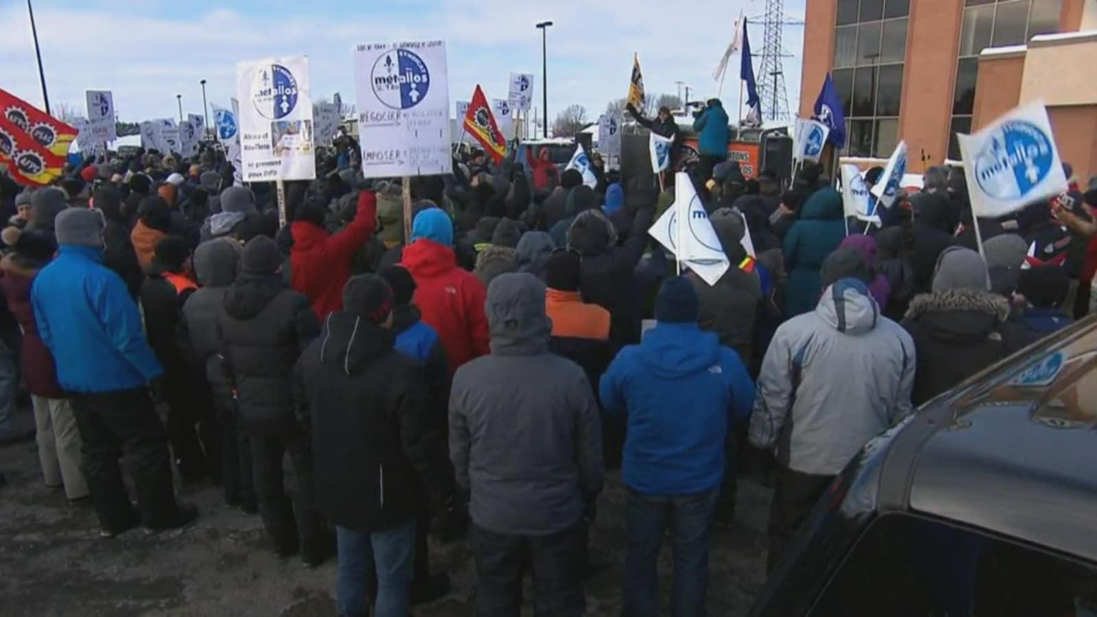 Des manifestants tiennent des pancartes alors qu'un homme s'adresse à eux en levant le poing.