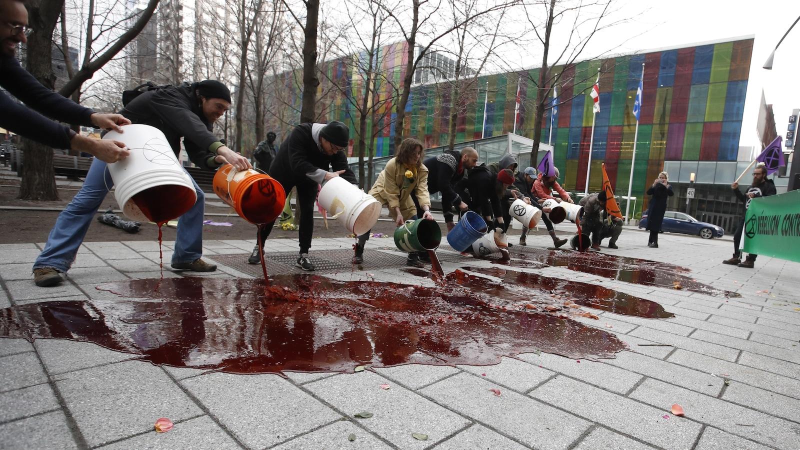 Une dizaine de manifestants vident des seaux remplis d'un liquide rouge.