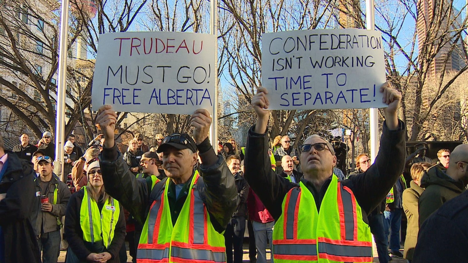 Deux manifestants à un ralliement en faveur de l'énergie pétrolière  portent des pancartes en faveur de l'indépendance de l'Alberta.