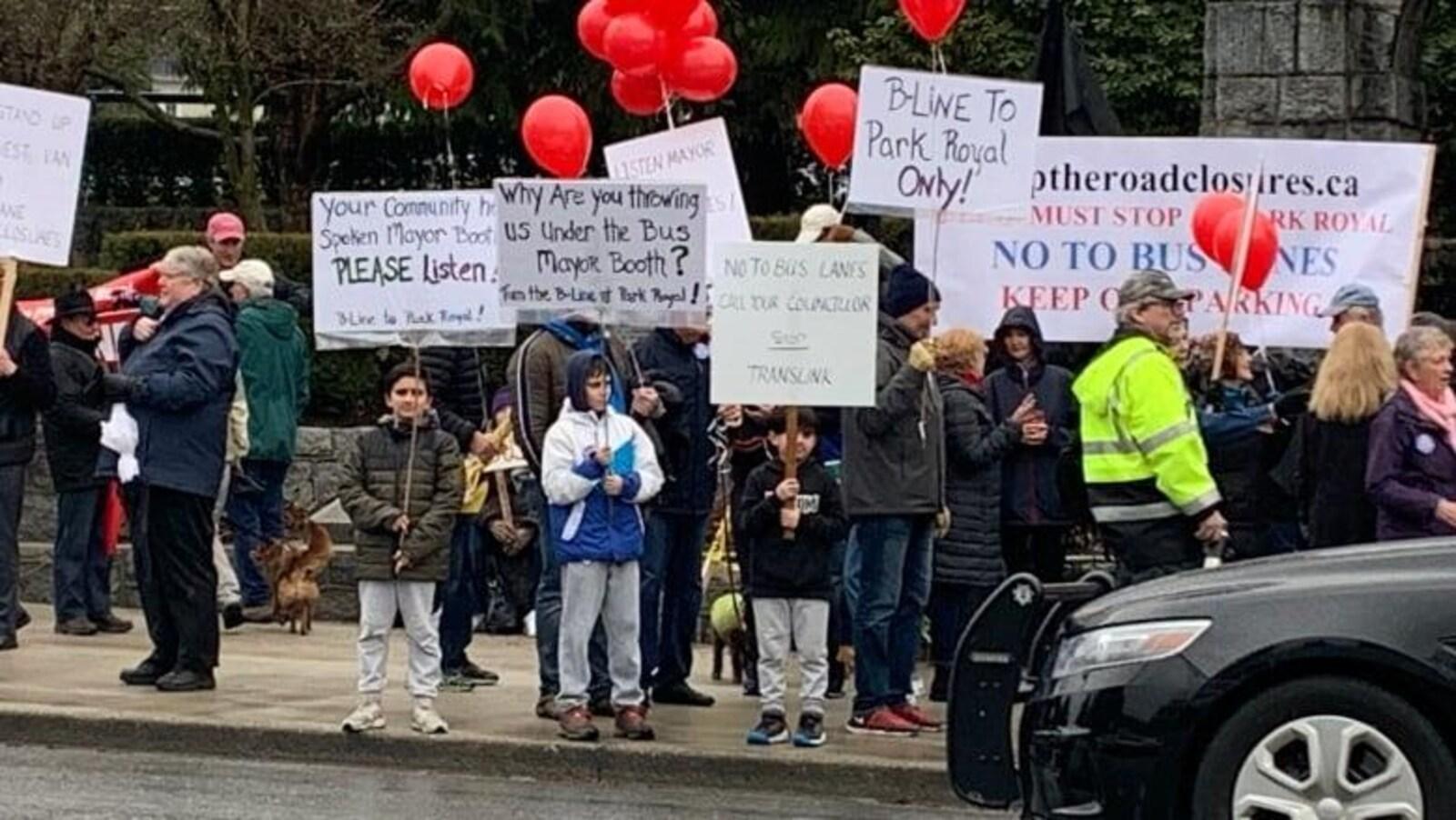 Des dizaines de manifestants brandissant des pancartes et tenant à la main des ballons rouges dénoncent un nouveau couloir d'autobus à West Vancouver.